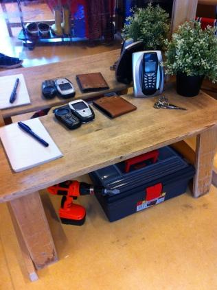 De 'sidetable' in de hal. Met natuurlijk de telefoons. En huissleutels, portemonnee en schrijfblok. Onder het tafeltje gereedschap voor de doe-het-zelver'.