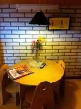 De eettafel, met bloemen en kleedje, de Allerhande en de afstandsbediening. De tv hangt rechts aan de muur.