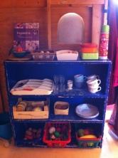 Van alles wat: servies, voorraad, kookboek, broodtrommels en thermosfles.